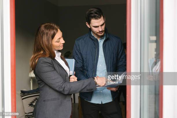 Female realtor assisting man while pointing at brochure by window