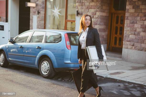 Female realtor carrying signboard and bag while walking on street in city