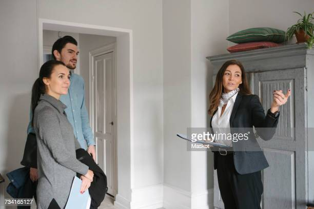 female realtor pointing while standing with young couple at home - real estate agent stock pictures, royalty-free photos & images