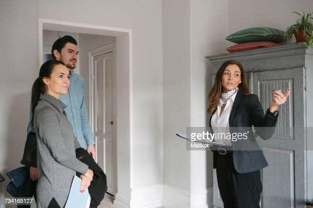 female realtor pointing while standing with young couple at home - agente inmobiliario fotografías e imágenes de stock