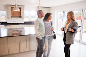 Female Realtor Showing Couple Interested In Buying Around House