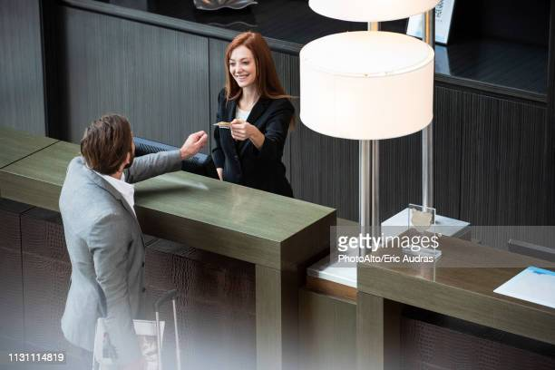 female receptionist giving credit card to businessman - hotel stock-fotos und bilder