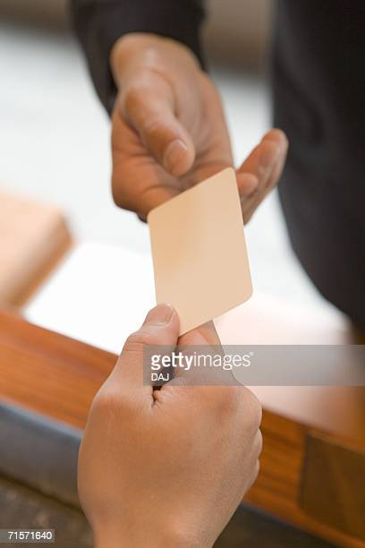 female receptionist handing over key to guest, close up, high angle view - hotel key stock photos and pictures