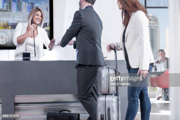Female receptionist handing reservation to businessman and woman at hotel reception desk