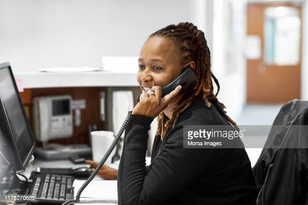 female receptionist talking on phone at desk - healthcare stock pictures, royalty-free photos & images