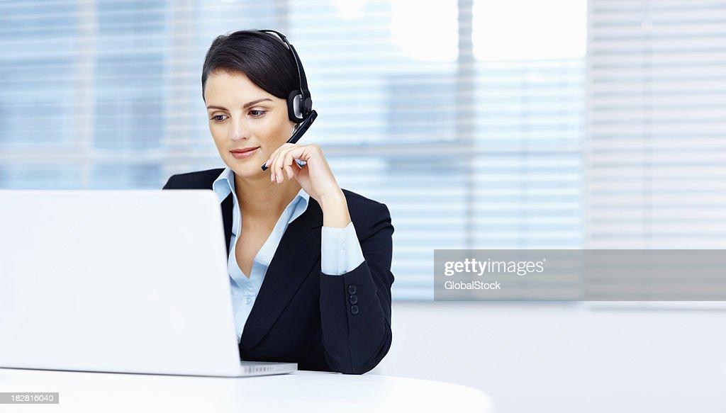 Réceptionniste femme travaillant sur ordinateur portable dans le