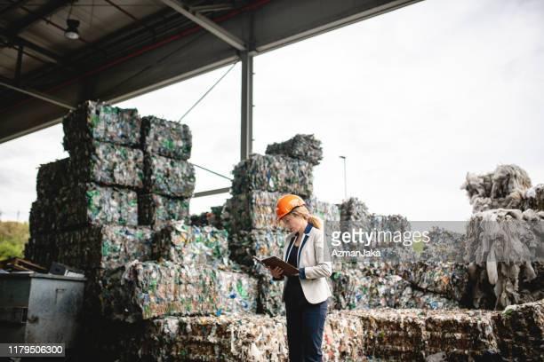 オーガナイザーにおける女性リサイクル検査官のチェックノート - 廃棄物処理 ストックフォトと画像