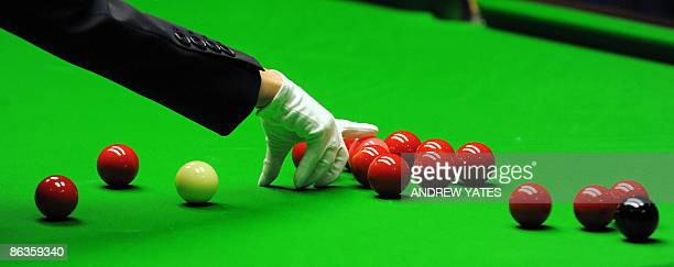 Female referee Michaela Tabb respots the pink ball during the World Championship Snooker final between Scotland's John Higgins and Britains Shaun...