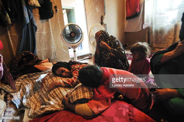 Female relatives of Gul Zada weep over her body moments after her body was brought home from the hospital after her death in the burn center of the...