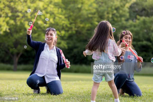 female relatives play bubbles during family reunion - aunt stock pictures, royalty-free photos & images