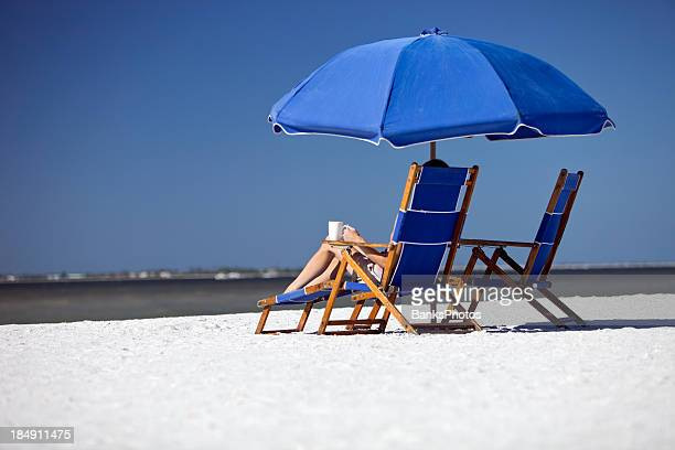 female relaxing on beach chair with coffee cup - fort myers beach stock pictures, royalty-free photos & images