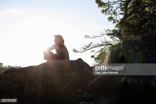 Female relaxing on rocks after exercising..