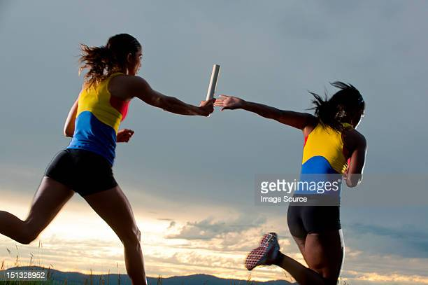Female relay racers passing baton
