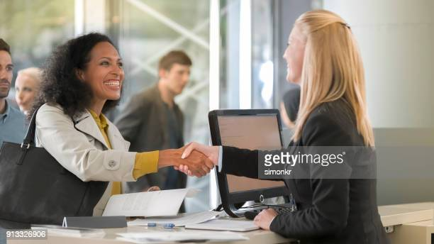 female rental clerk giving documents to female customer renting car - cashier stock pictures, royalty-free photos & images
