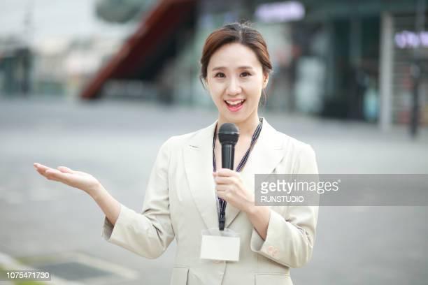 female reporter holding microphone - apresentador imagens e fotografias de stock