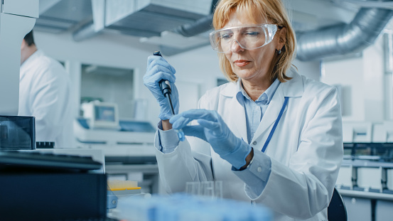 Female Research Scientist Uses Micro Pipette while Working with Test Tubes. People in Innovative Pharmaceutical Laboratory with Modern Medical Equipment for Genetics Research. 1140779660