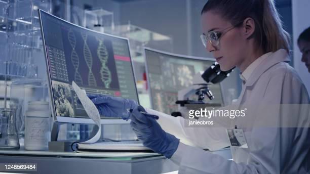 weibliches forschungsteam untersucht dna-mutationen. computerbildschirme mit dna-helix im vordergrund - wissenschaftlerin stock-fotos und bilder