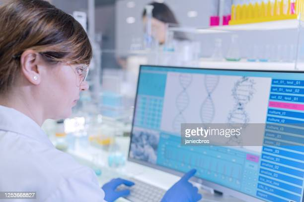 female research team studying dna samples. computer screens with dna helix in foreground - genetic research stock pictures, royalty-free photos & images
