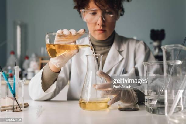 investigadora femenina examinando un líquido amarillo en un frasco erlenmeyer en un laboratorio - frasco cónico fotografías e imágenes de stock