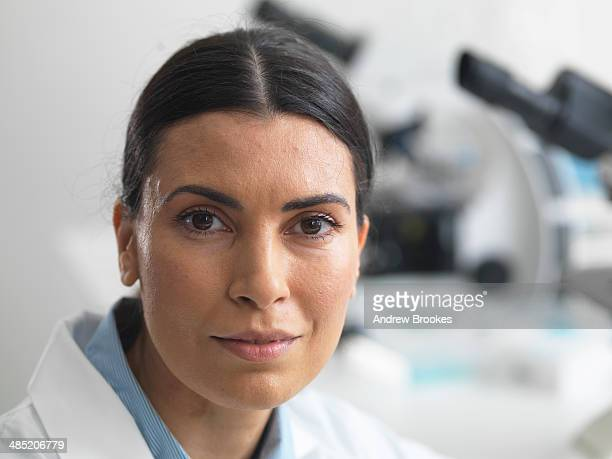 female researcher in laboratory next to microscopes. - microbiologist stock pictures, royalty-free photos & images