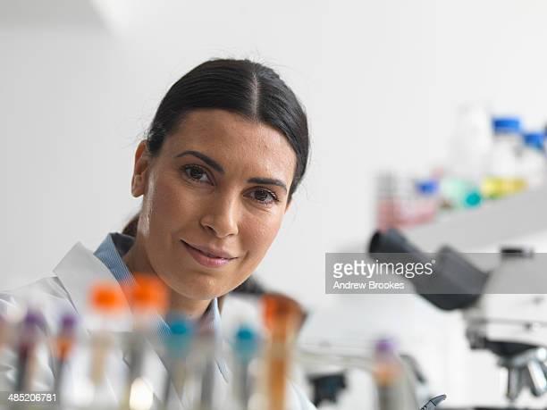 Female researcher in laboratory next to microscopes.