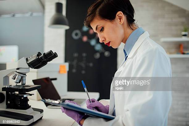 female researcher working in her lab. - physicist stock pictures, royalty-free photos & images