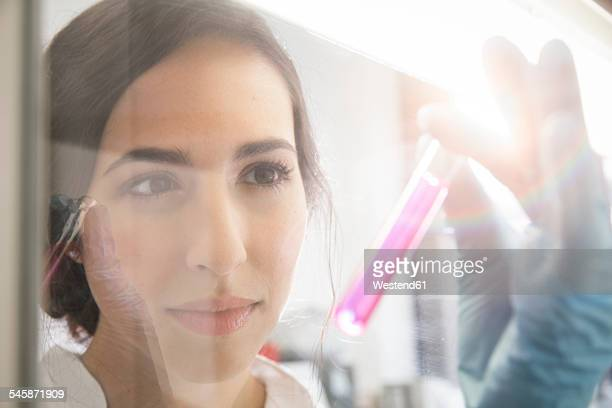 female researcher working in laboratory - pink tube photos et images de collection