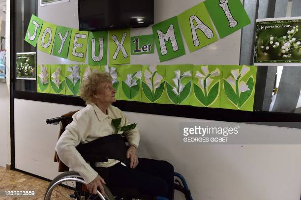Female resident at the Henri IV retirement passes a banner that reads, 'Happy May 1st' and decorated with images of Lily of the Valley or Muguet...