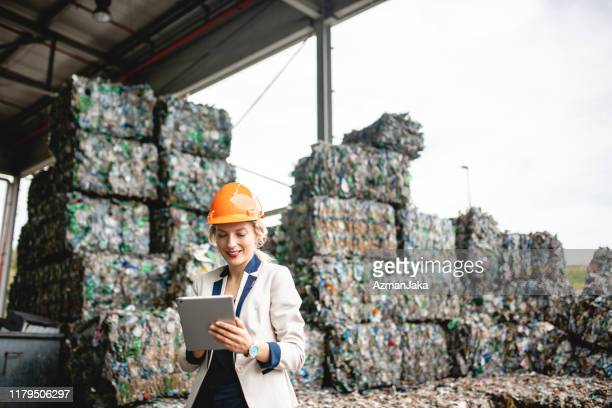 female resource recovery specialist using digital tablet - social responsibility stock pictures, royalty-free photos & images