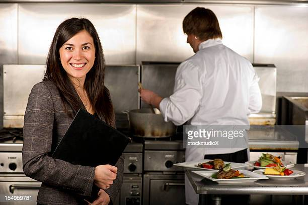 Female restaurant manager in kitchen with chef