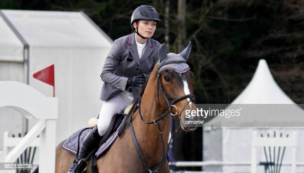female rider jumping an obstacle on chestnut horse - equestrian helmet stock pictures, royalty-free photos & images
