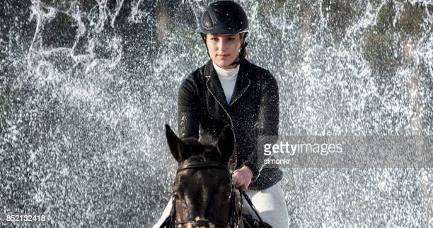 female rider jumping through waterfall on her horse - riding boot stock pictures, royalty-free photos & images