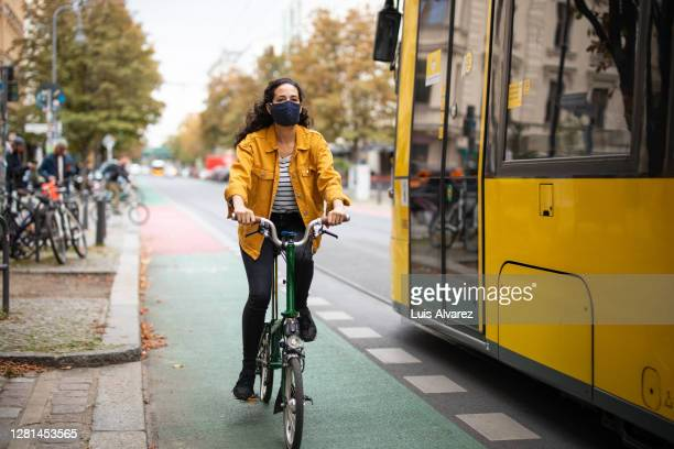 female riding a cycle wearing face mask in the city - bicycle lane stock pictures, royalty-free photos & images