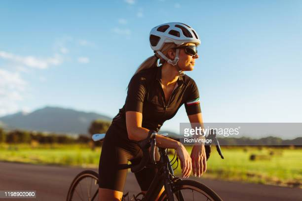 female riding road bike in summer - one mid adult woman only stock pictures, royalty-free photos & images
