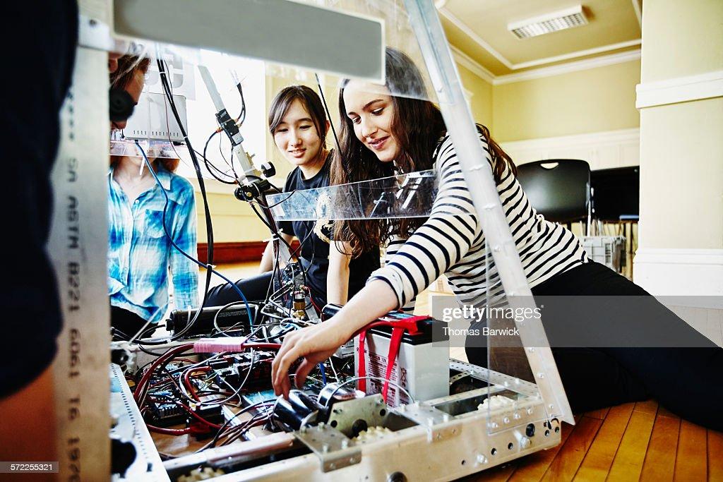 Female robotics team working on wiring of robot : Stock Photo