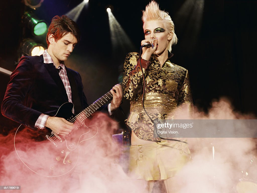Female Rock Band Singer With a Gold Mini-Skirt and Blond Quiff and a Male Guitarist Perform on a Smoky Stage : Stock Photo