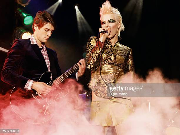 Female Rock Band Singer With a Gold Mini-Skirt and Blond Quiff and a Male Guitarist Perform on a Smoky Stage