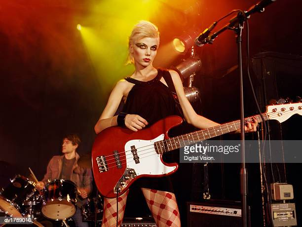 female rock band singer with exaggerated eye make-up and a blond quiff stands on stage with an electric guitar, drummer in the background - blonde female singers stock photos and pictures