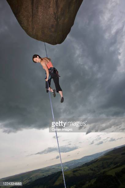 female rock climber descending cliff at the peak district in england - individual event stock pictures, royalty-free photos & images