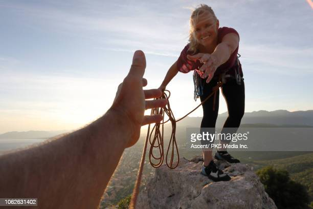 female rock climber extends a helping hand to teammate - tendere la mano foto e immagini stock