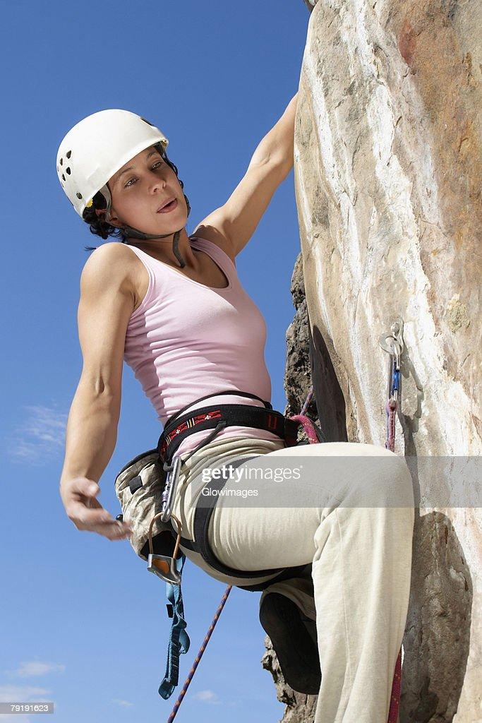 Female rock climber scaling a rock face : Stock Photo