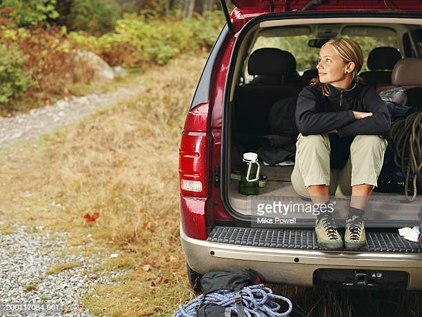 female rock climber sitting in back of suv, looking outward - car trunk stock pictures, royalty-free photos & images