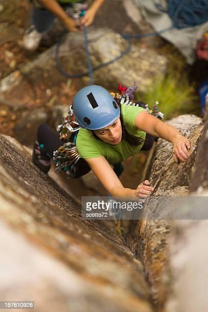 A female rock climbing a tall wall