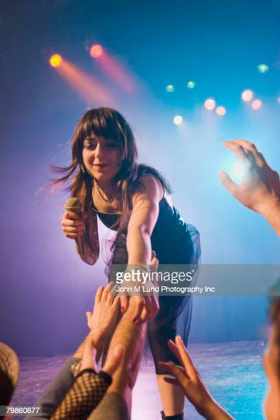 Female rock star on stage interacting with audience