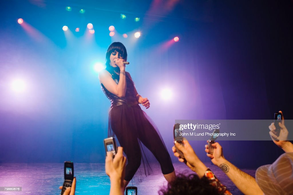 Female rock star performing in front of audience : Stock Photo
