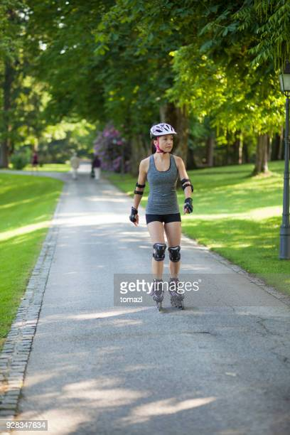 female roller skater in park - padding stock photos and pictures