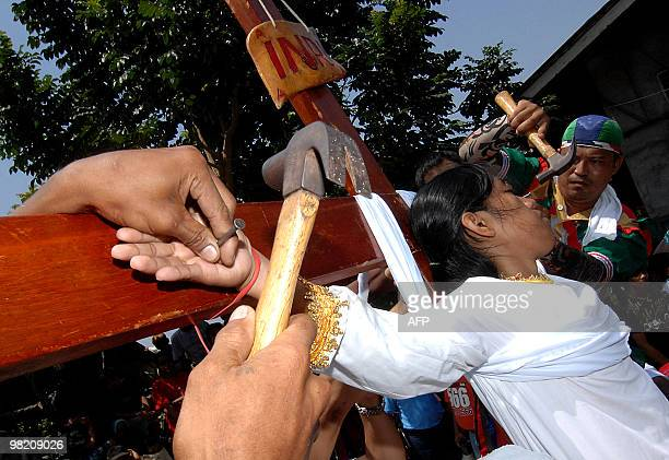 Female Roman Catholic devotee Maria Wendelyn Pedrosa is nailed to a cross during the reenactment of the crucifixion of Jesus Christ in Paombong...