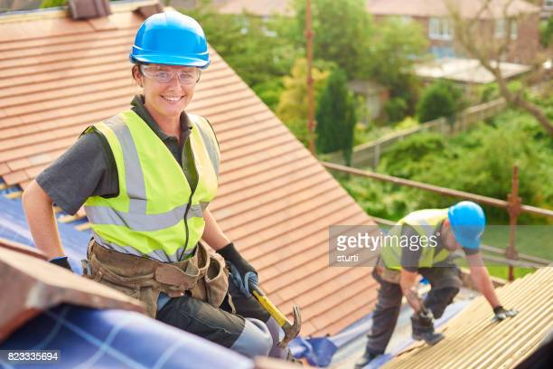 female roofer replacing roof tiles
