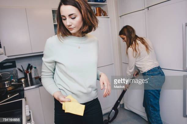 Female roommates cleaning kitchen in college dorm
