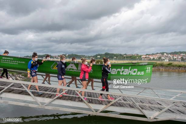 Female rowers with protective face masks carry the boat to dock for the first training session since the confinement began in March, on June 08, 2020...